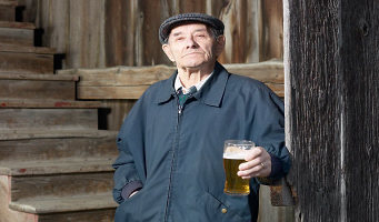 Elderly man drinking glass of beer in old wooden barn.jpg